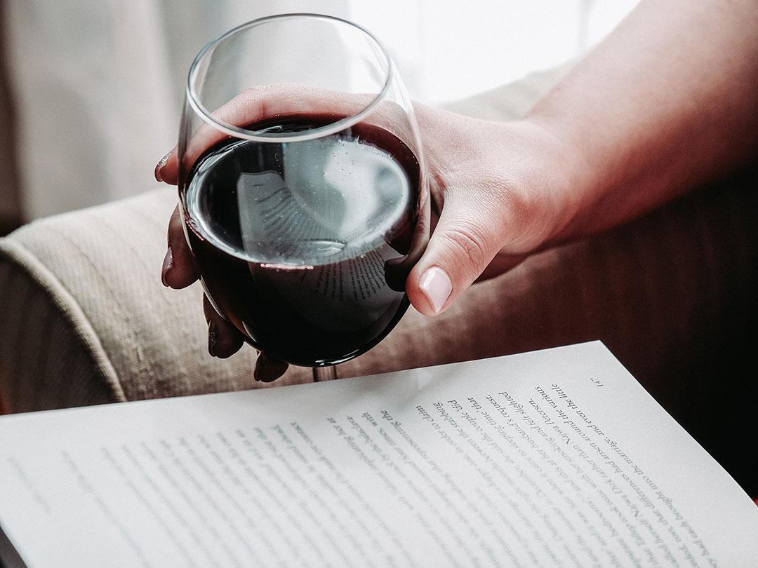 Person dricker rödvin och läser en bok i sin ensamhet