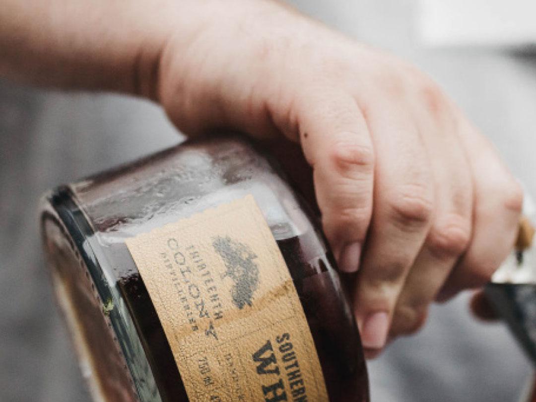 Person häller upp ett glas whiskey