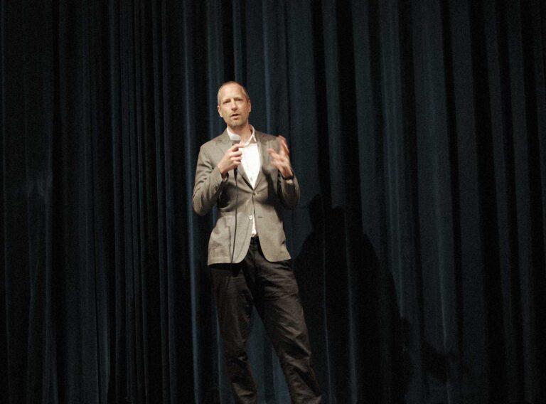 Carl Sundevall föreläser om alkohol och beroende framför ett draperi